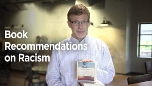 Peter Hubbard holding a book about racism
